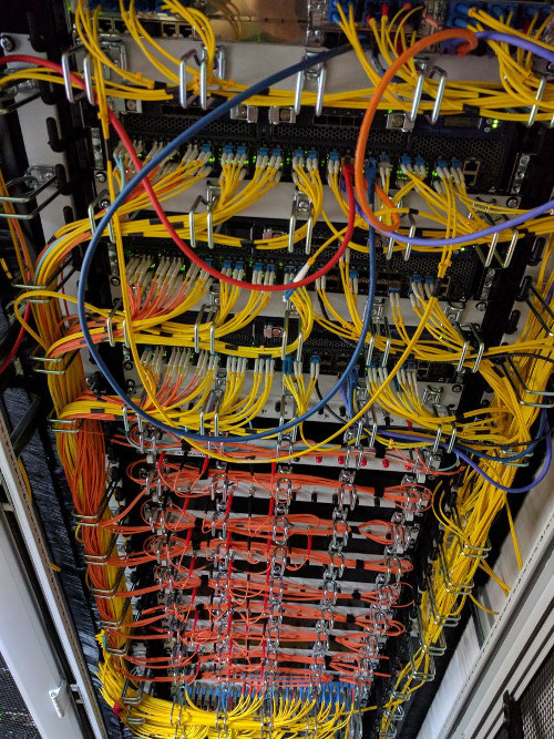 Photo of rack with 3 big routers and lots of fiberoptic patchpanels. // Foto eines Racks mit 3 großen Routern und vielen Glasfaserpatchpaneln.